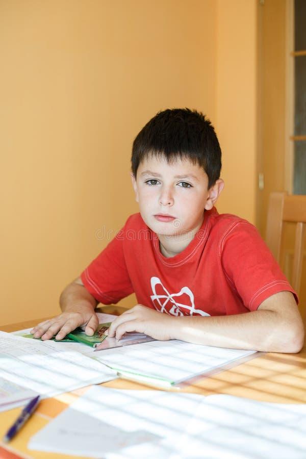 Junge, der Schulhausarbeit tut stockfoto