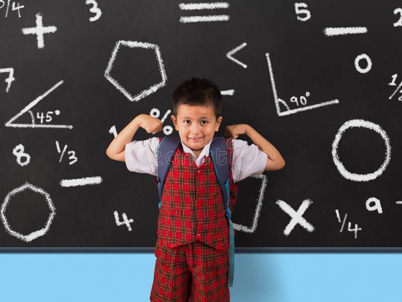 Junge in der Schuluniform, die seine Muskeln vor Tafel biegt lizenzfreie stockfotografie
