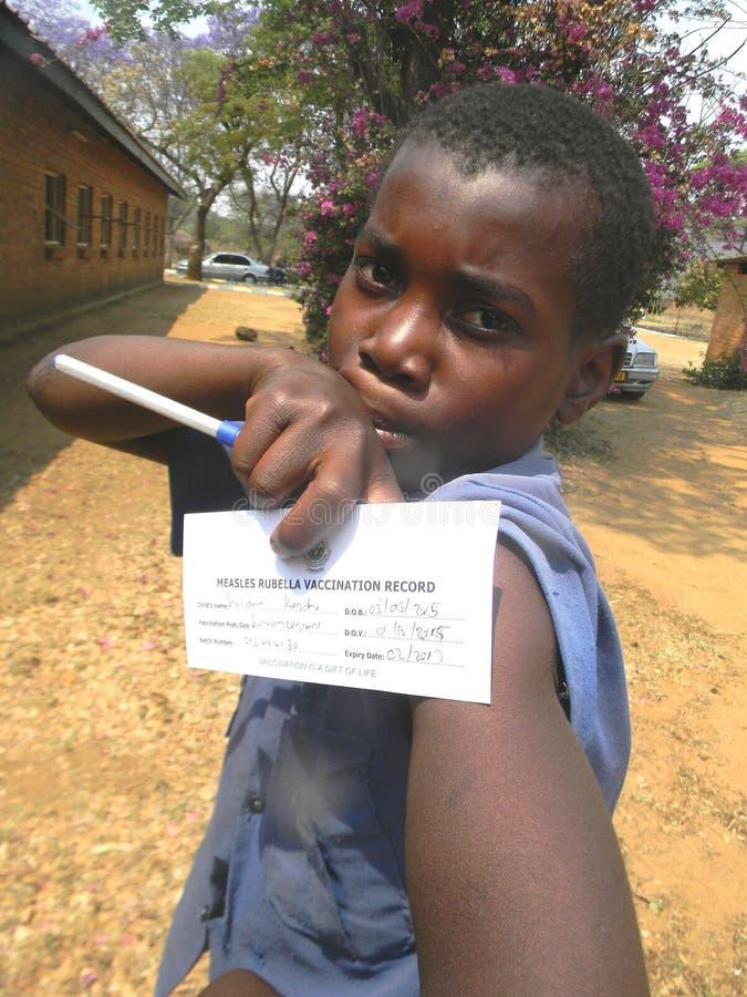 Junge, der Schutzimpfungskarte hält lizenzfreies stockfoto