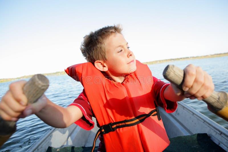 Junge, der sein eigenes Boot rudert lizenzfreie stockfotografie