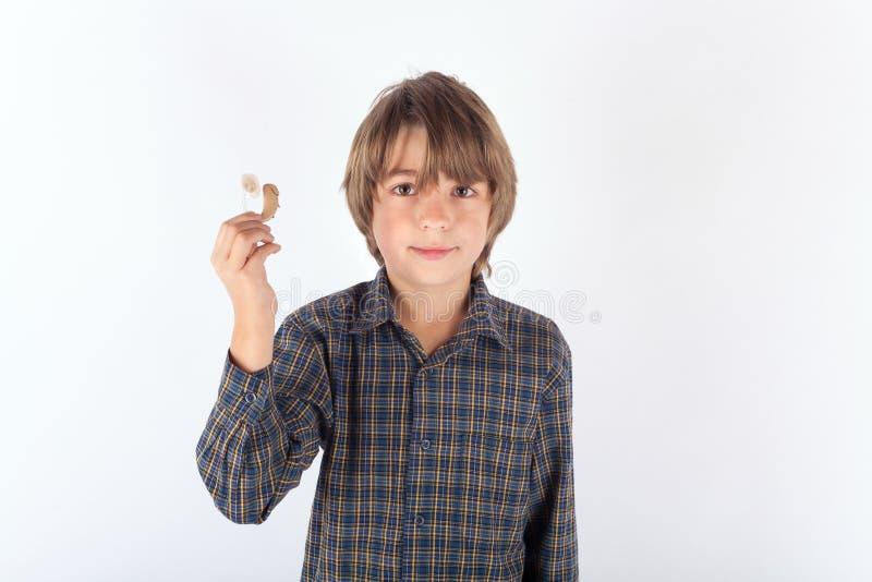 Junge, der sein Hörgerät zeigt stockbild
