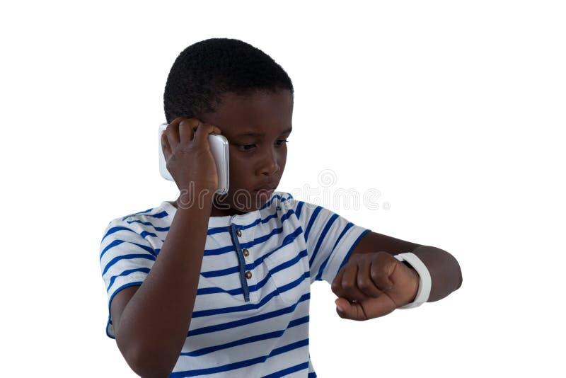Junge, der seine intelligente Uhr bei der Unterhaltung am Handy betrachtet lizenzfreies stockfoto