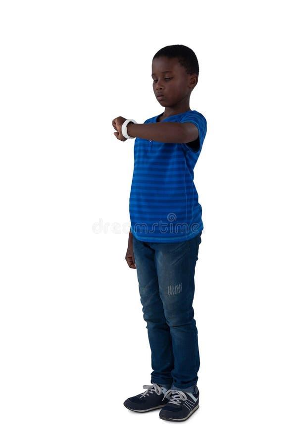 Junge, der seine intelligente Uhr betrachtet stockfotos