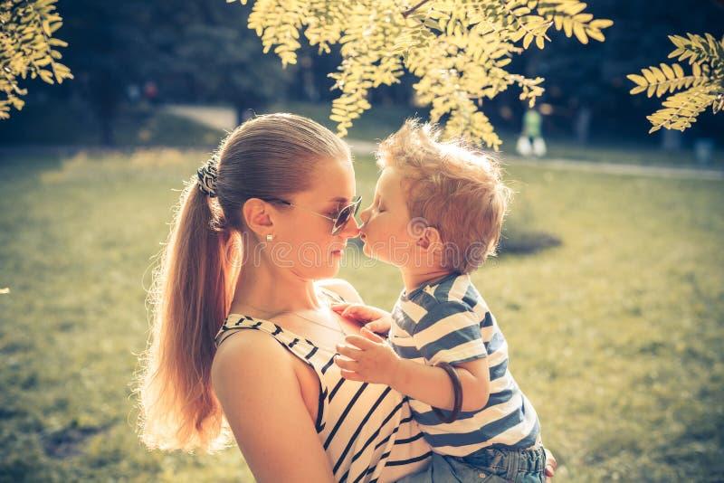 Junge, der seine Mutter küsst lizenzfreie stockbilder