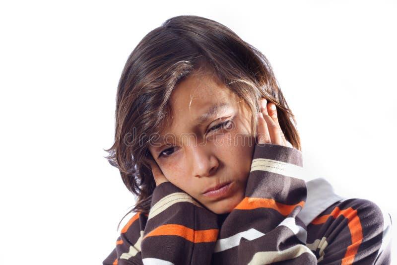 Junge, der seine Ohren abdeckt stockfotos