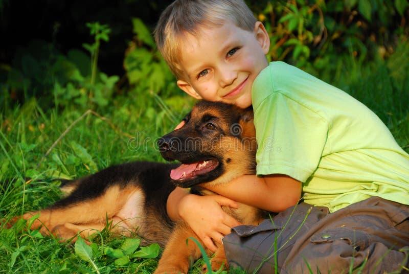 Junge, der seinen Hund umarmt stockfotografie