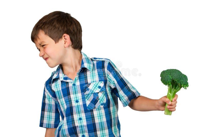 Junge, der seinen Kopf weg von einem Brokkoli-Bündel dreht lizenzfreie stockbilder