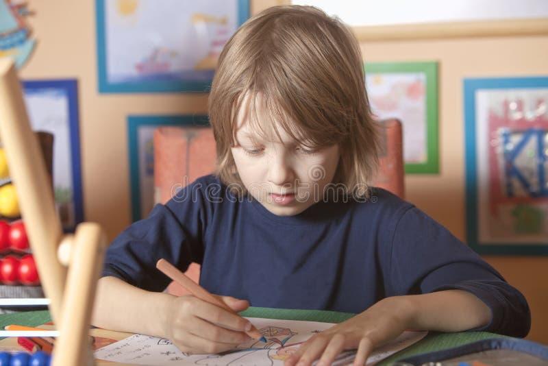 Junge, der an seiner Heimarbeit arbeitet lizenzfreie stockbilder