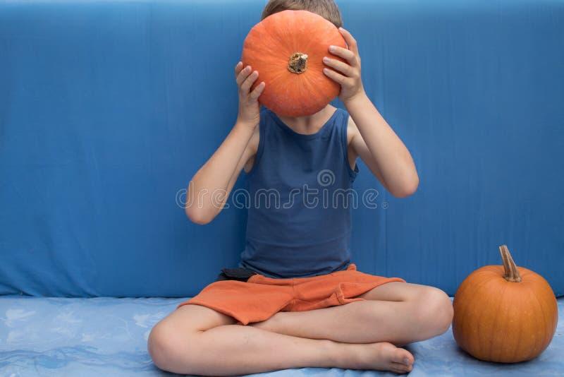 Junge, der sich auf dem blauen Hintergrund mit Kürbisen hinsetzt Buntes Halloween oder gesundes Lebensstildesign stockfotos