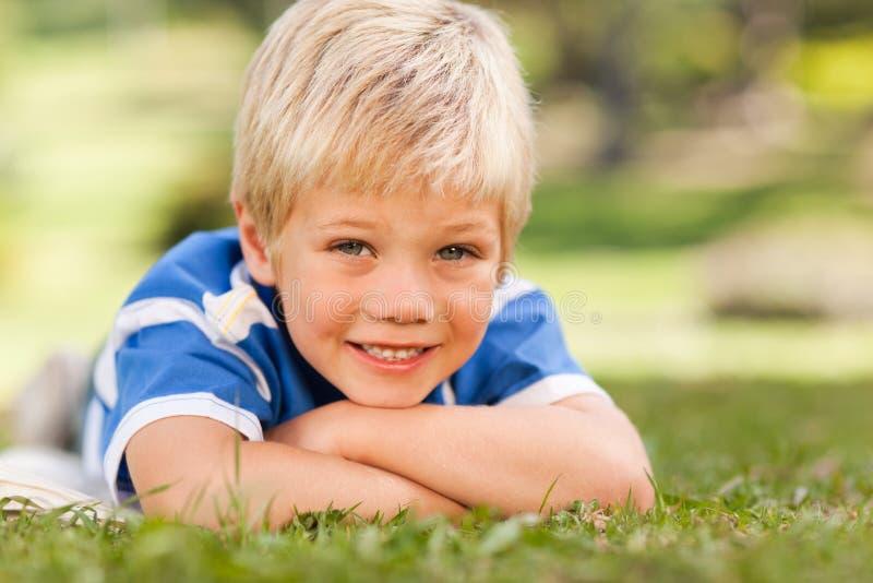 Junge, der sich im Park hinlegt stockbilder
