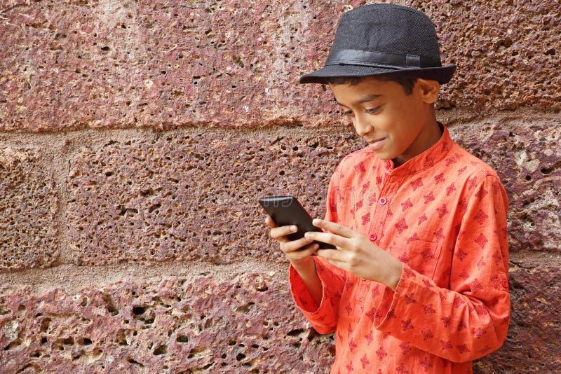 Junge, der Smartphone genießt lizenzfreie stockfotos