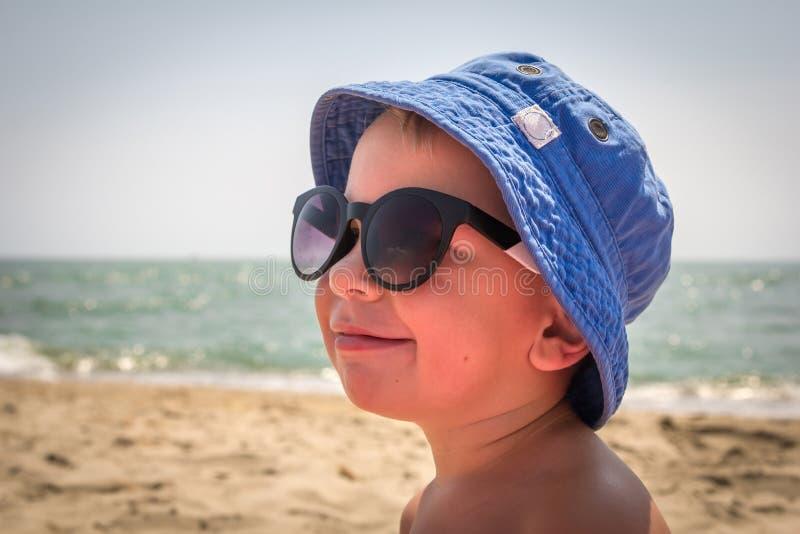 Junge in der Sonnenbrille auf dem Strand lizenzfreie stockfotos