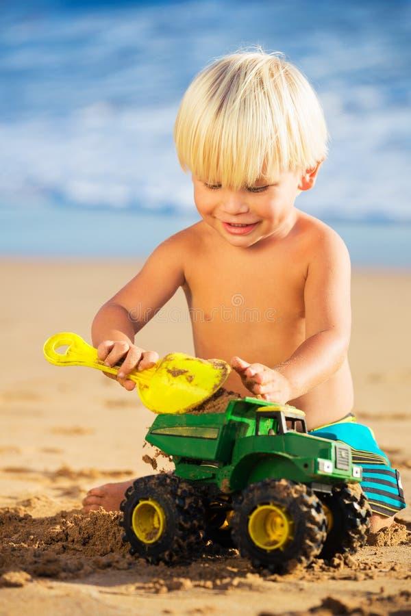 Junge, der am Strand spielt stockfotos