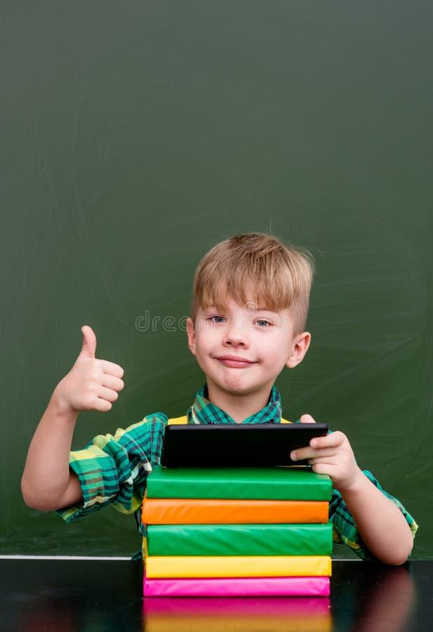 Junge, der Tablet-Computer verwendet und sich Daumen zeigt lizenzfreies stockfoto