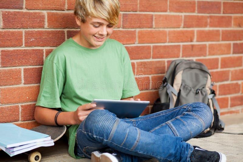 Junge, der Tablettecomputer verwendet stockbild
