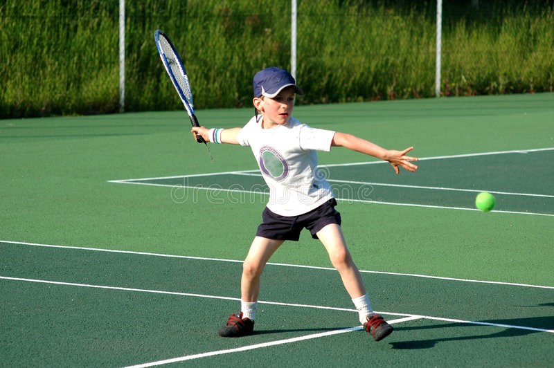 Junge, der Tennis spielt stockbild