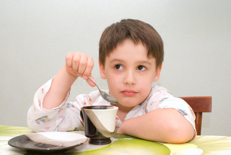 Junge, der am Tisch isst lizenzfreies stockbild