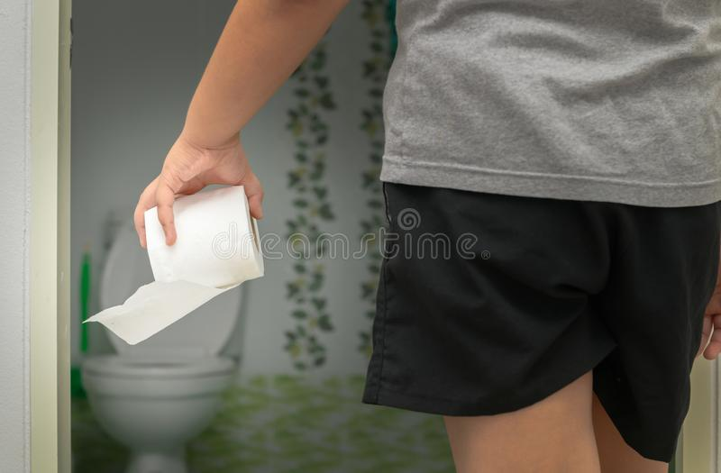 Junge, der Toilettengeweberolle vor Badezimmer hält stockfotografie