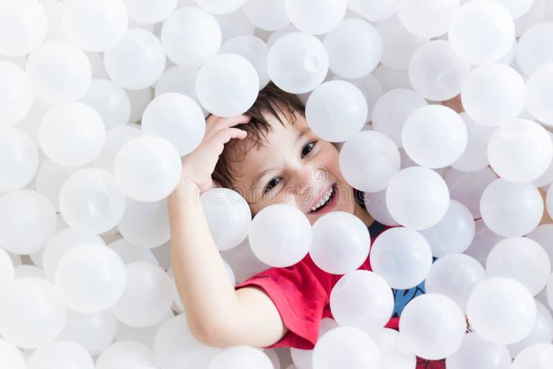 Junge, der unter weißen Bällen am Spielplatz sich versteckt lizenzfreie stockbilder
