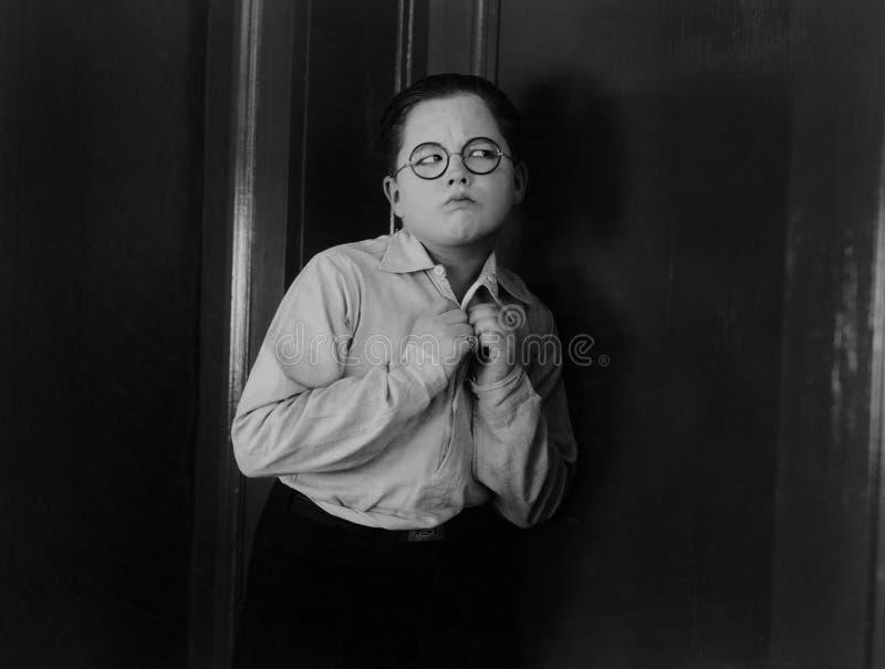 Junge, der versucht zu hören, sein Ohr an einer Tür setzend (alle dargestellten Personen sind nicht längeres lebendes und kein Zu lizenzfreies stockfoto