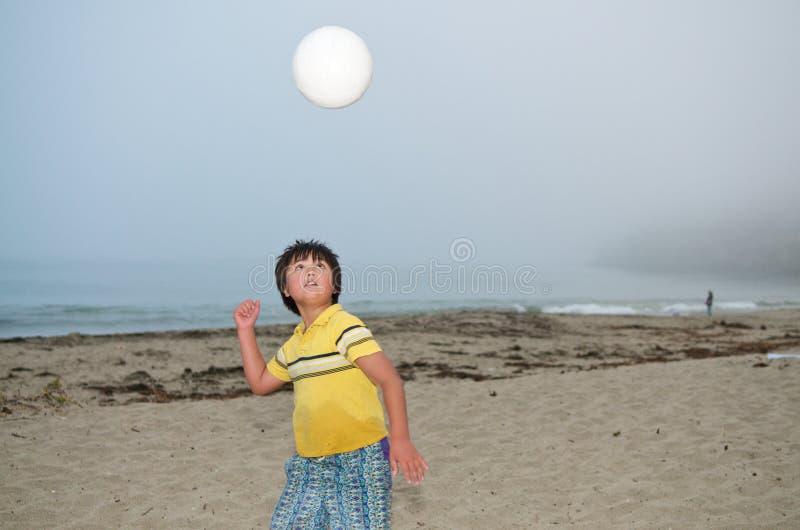 Junge, der Volleyball spielt stockfotografie