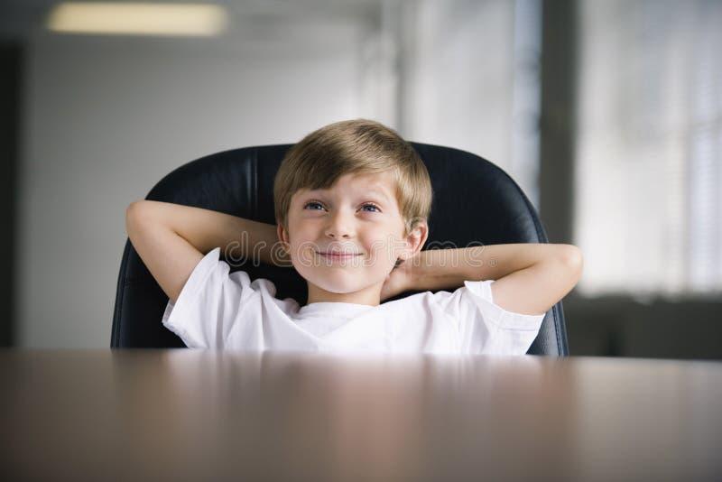 Junge, der vom Geschäftssitzungssaalstuhl lächelt stockfotos