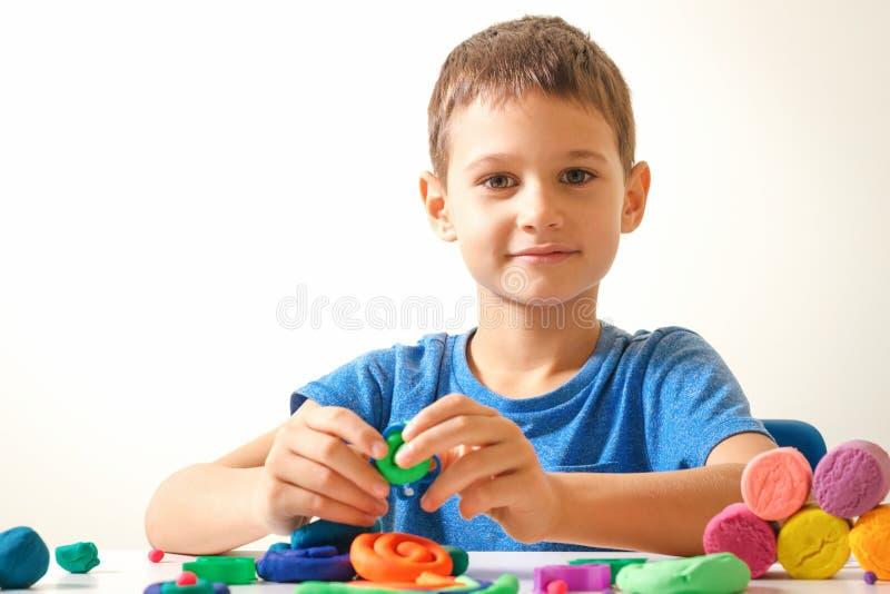 Junge, der vom Modellierton oder vom Plasticine spielt und schafft stockfotografie