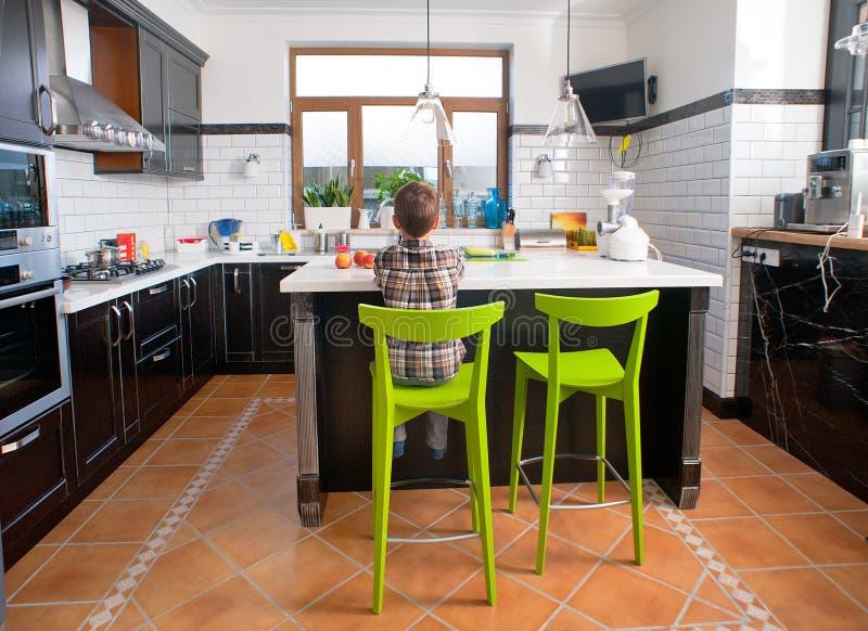 Junge, der vor Tabelle in der Küche sitzt stockfotos