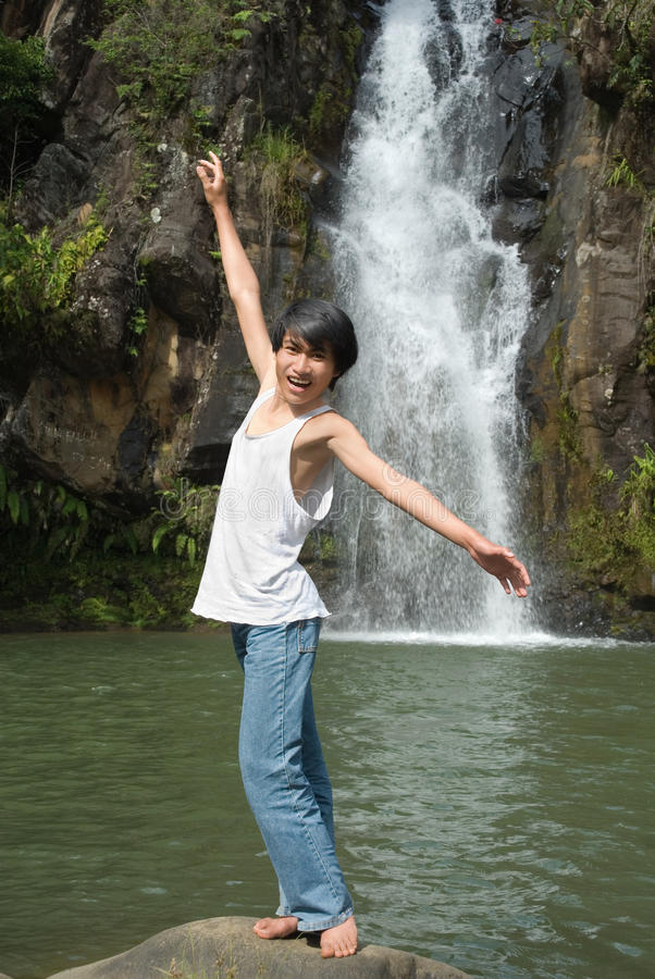Junge, der am Wasserfall balanciert stockfoto