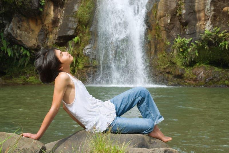 Junge, der am Wasserfall sich entspannt lizenzfreies stockfoto