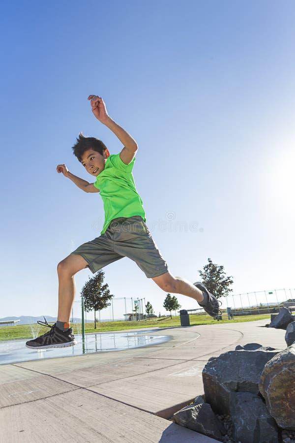 Junge, der weg von einem Felsen springt stockfoto