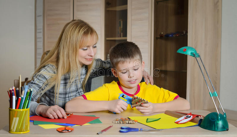 Junge, der Weihnachtsdekorationen mit seiner Mutter macht Machen Sie Weihnachtsdekoration mit Ihren eigenen Händen lizenzfreie stockfotografie