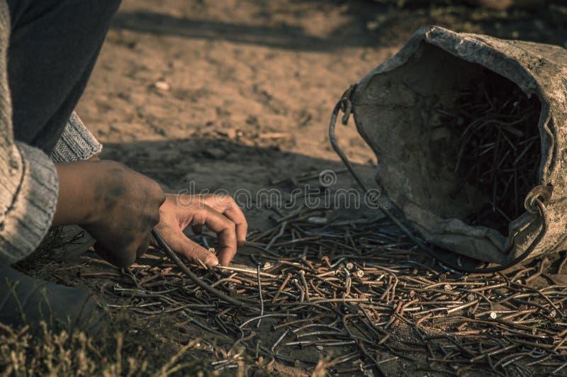 Junge, der zerstreute rostige Nägel sammelt stockbilder