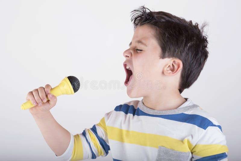 Junge, der zum Mikrofon singt stockfoto