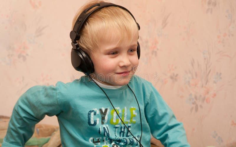 Junge, der zur Musik in den Kopfhörern littening ist stockfotografie
