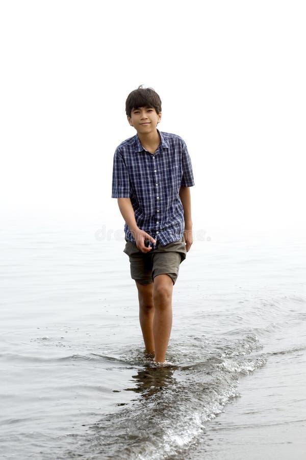 Junge des jungen jugendlich, der entlang Strand watet stockfoto