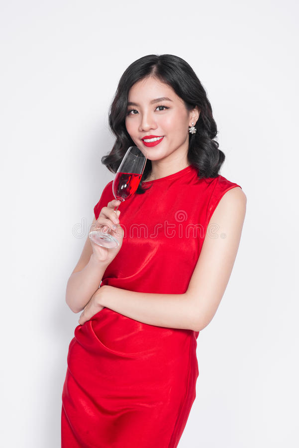 Junge, die asiatische Frau im roten Kleid hält Weinglas feiern stockbilder