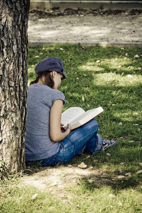 Junge, die ein Buch genießen stockbild