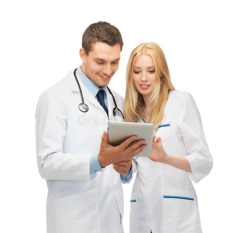 Junge Doktoren, die mit Tabletten-PC arbeiten stockbild