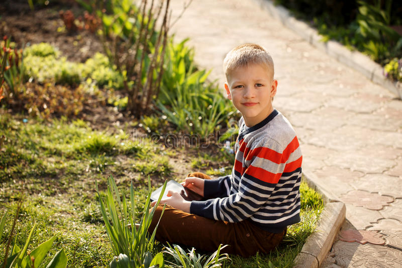 Junge draußen auf dem Gras am Hinterhof unter Verwendung seiner Tabletten-COM stockfotografie