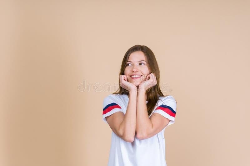 Junge durchdachte Frau, die weg, stehend auf beige Pastellhintergrund schaut lizenzfreies stockbild