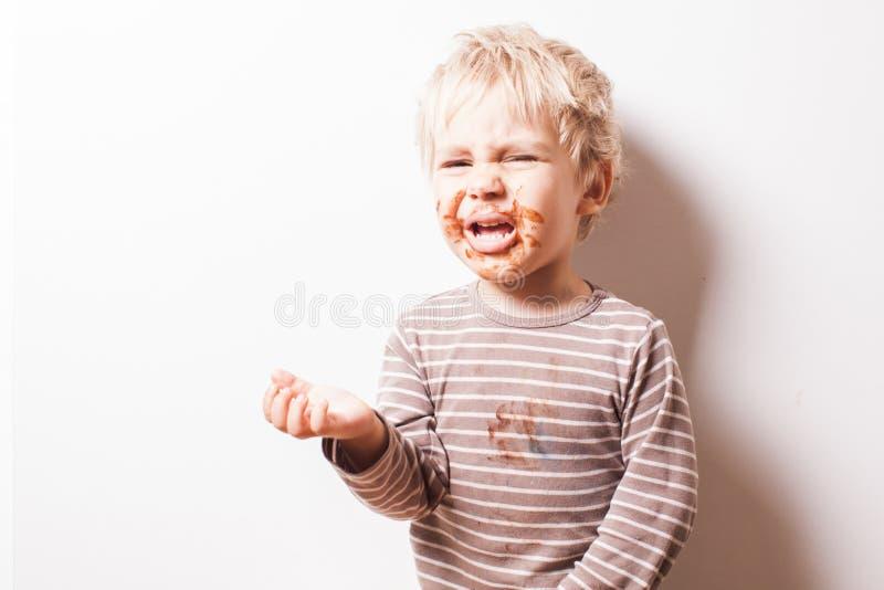Junge eated Schokolade und wünscht mehr essen stockfotografie