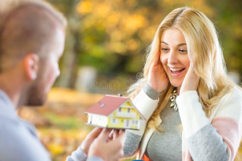 Junge Ehemannüberraschungen mit neuem Familienhaus stockbild