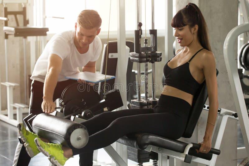 junge Eignungsfrau in den Sportkleidungsübungs-Beinmuskeln mit Stoßmaschine mit persönlichem Trainer in der Turnhalle Sportm?dche stockfotos