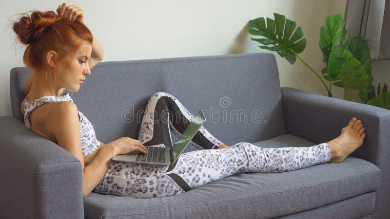 junge Eignungsfrau in der Sportkleidung, die das Yoga ausdehnt Bein während unter Verwendung des Laptop- oder Computernotizbuches stockbilder