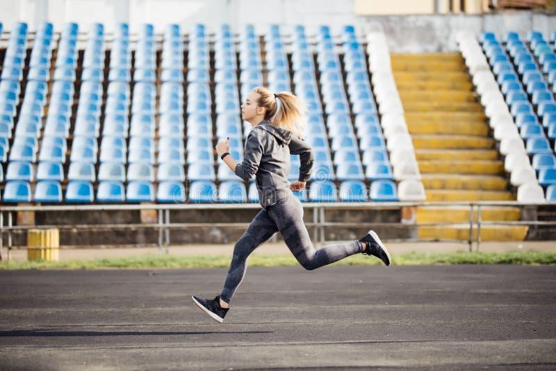 Junge Eignungsfrau, die während des sonnigen Morgens auf Stadionsbahn läuft lizenzfreies stockbild