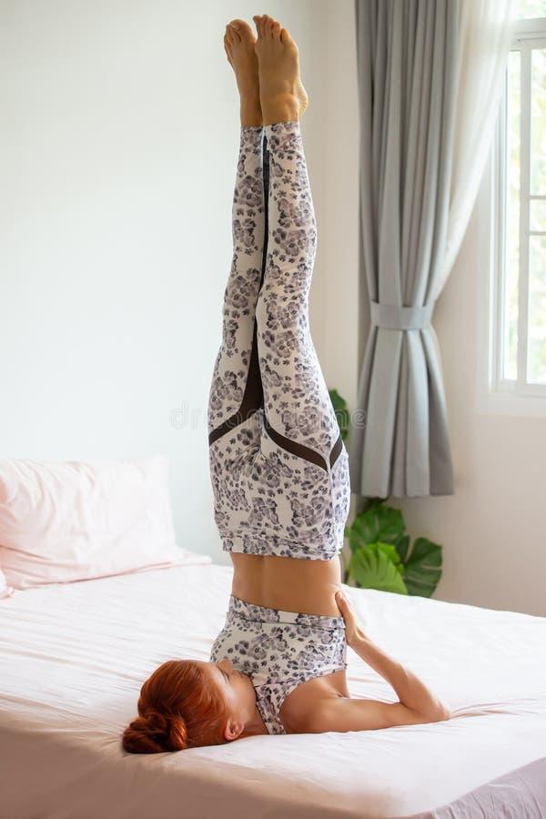 Junge Eignungsfrau in sportwear übendem Yoga auf Bett im Schlafzimmer zu Hause am Morgen Sportmädchen, das gestützte Kerze tut lizenzfreie stockfotografie