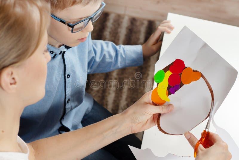 Junge in einem blauen Hemd mit Mama Die Mutter des Jungen schneidet Scheren mit einer Plastikarbeit, die von einem Kind erledigt  lizenzfreie stockbilder