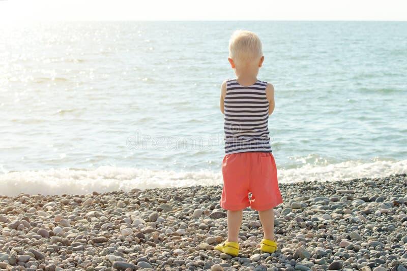 Junge in einem gestreiften T-Shirt steht auf dem Strand und betrachtet das Meer Rückseitige Ansicht lizenzfreies stockfoto