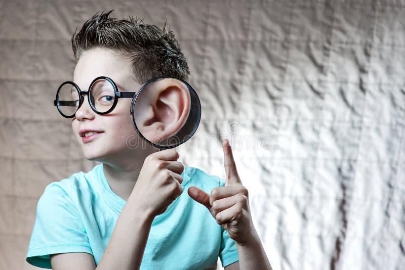 Junge in einem hellen T-Shirt lehnte seine Tatze zu seinem Ohr, von dem sie stark wuchs lizenzfreie stockbilder
